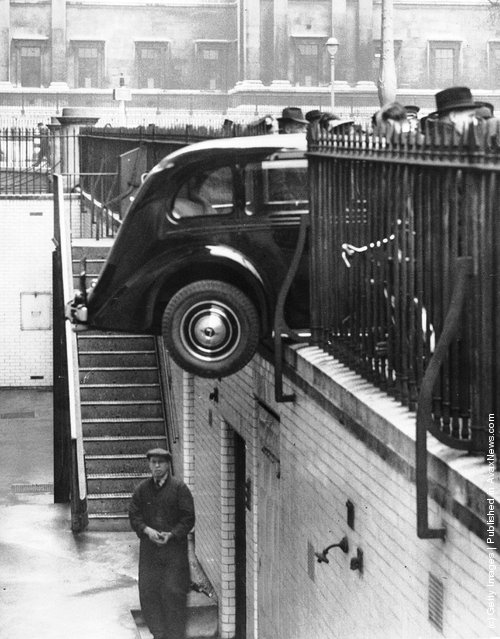 1939: A car hangs precariously over the basement of Canada House in Trafalgar Square, having crashed through the railings