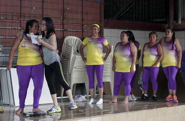 Andrea Abarca (R) congratulates Hazel Castillo after announcing that she lost 7 kilograms, before an aerobics class in Los Guidos de Desamparados July 23, 2015. Castillo lost 7 kilograms in six months while participating in the health program organized by Abarca, which aims to combat obesity and sedentary behavior in poor women living in a slum. (Photo by Juan Carlos Ulate/Reuters)