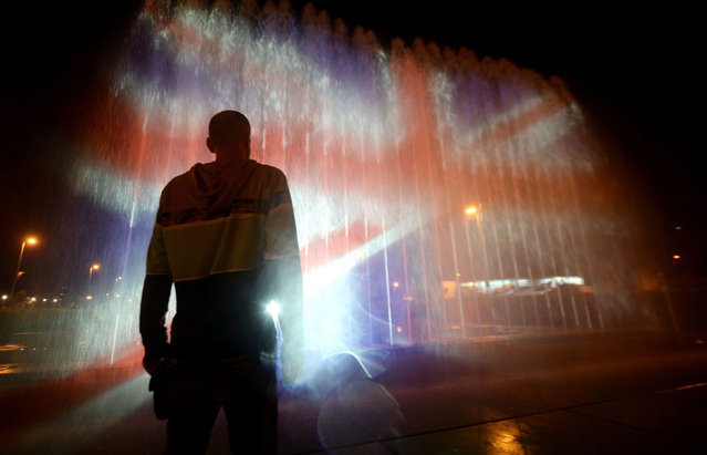 A man stands in front of a fountain illuminated with the colours of the United Kingdom flag on May 23, 2017, in Zagreb, during a tribute to victims of an attacks claimed by Islamic State which killed at least 22 people and left more than 60 injured in Manchester the day before. Twenty two people have been killed and dozens injured in Britain' s deadliest terror attack in over a decade after a suspected suicide bomber targeted fans leaving a concert of US singer Ariana Grande in Manchester. British police on May 23 named the suspected attacker behind the Manchester concert bombing as Salman Abedi, but declined to give any further details. (Photo by AFP Photo/Stringer)