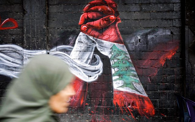 This picture taken on October 24, 2019 in the northern Lebanese city of Tripoli shows a woman passing by graffiti depicting two hands holding each other, both painted in the colours of the Lebanese national flag, painted by Palestinian refugee Ghayath al-Rawbeh, who was originally a Palestinian refugee in Syria and fled with the start of the Syrian crisis, painted on a wall at al-Nour Square in the city centre. (Photo by Ibrahim Chalhoub/AFP Photo)