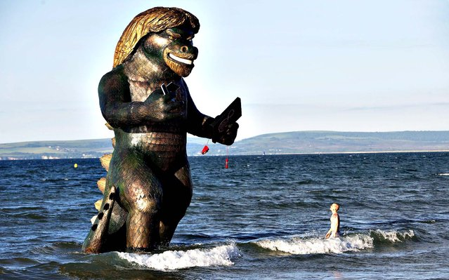 A 25 foot high sea creature resembling Richard Branson emerges from the sea on Bournemouth beach in Dorset carrying a TV, laptop, phone and mobile to celebrate the launch of Virgin Media's Big Kahuna quad-play bundle. (Photo by David Parry/PA Wire)