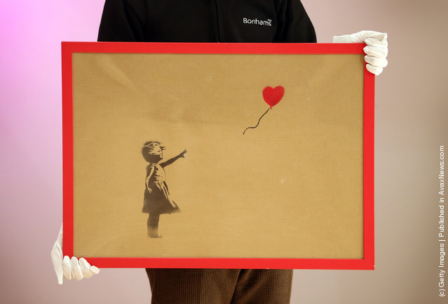 An employee holds Banksy's 'Girl and Balloon' which was painted on an Ikea frame at Bonhams auctioneers
