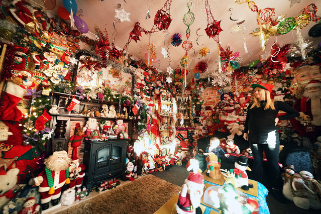 Victoria Burnham, 25, puts the finishing touches to hundreds of Santas and other festive decorations at her father's house in Framwellgate Moor in County Durham, England on December 4, 2019 ahead of the Christmas period. (Photo by Owen Humphreys/PA Images via Getty Images)