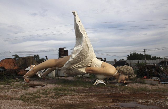 """A giant statue of U.S. actress Marilyn Monroe is seen at the dump site of a garbage collecting company in Guigang, Guangxi Zhuang Autonomous Region June 18, 2014. The eight-metre-tall stainless steel statue, which weighs about eight tonnes, was made by several Chinese artists for over two years, based on the famous scene from her movie """"The Seven Year Itch"""". (Photo by Reuters/China Daily)"""