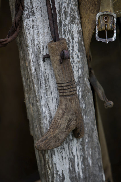 In this May 16, 2017 photo, a handmade whip handle, in the shape of a boot, hangs in a cowboy camp in Corumba, in the Pantanal wetlands of Mato Grosso do Sul state, Brazil. The whip was made by one of the ranch hands who helps round up cattle. (Photo by Eraldo Peres/AP Photo)