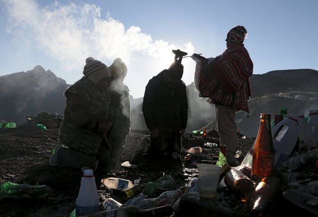 "A witch doctor makes a ritual for a family at ""La Cumbre"" a place for offerings to goddess ""Pachamama"" near La Paz, August 1, 2015. (Photo by David Mercado/Reuters)"