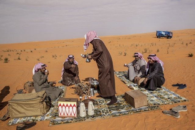 Local spectators drink tea and coffee on the dunes during stage six of the Dakar Rally between Hail and Riyadh, Saudi Arabia, Friday, January 10, 2020. (Photo by Bernat Armangue/AP Photo)