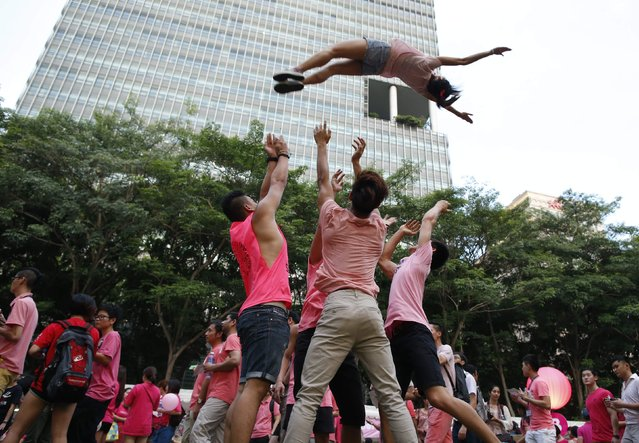 Participants dressed in pink perform cheerleading stunts before taking part in the forming of a giant pink dot at the Speakers' Corner in Hong Lim Park in Singapore June 28, 2014. The annual Pink Dot Sg event promotes an acceptance of the Lesbian, Gay, Bisexual and Transgender (LGBT) community in Singapore, according to organizers. (Photo by Edgar Su/Reuters)