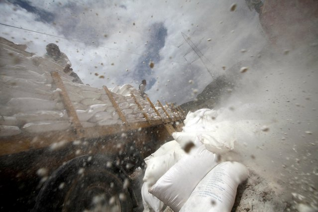Workers dispose of sacks of wheat flour which reportedly expired after they were provided by the World Food Program (WFP), on the outskirts of Sanaa, Yemen August 28, 2019. (Photo by Mohamed al-Sayaghi/Reuters)