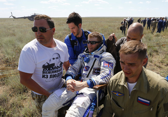 Ground personnel carry International Space Station crew member Britain's Tim Peake shortly after landing near the town of Dzhezkazgan, Kazakhstan, Saturday, June 18, 2016. (Photo by Shamil Zhumatov/Pool Photo via AP Photo)