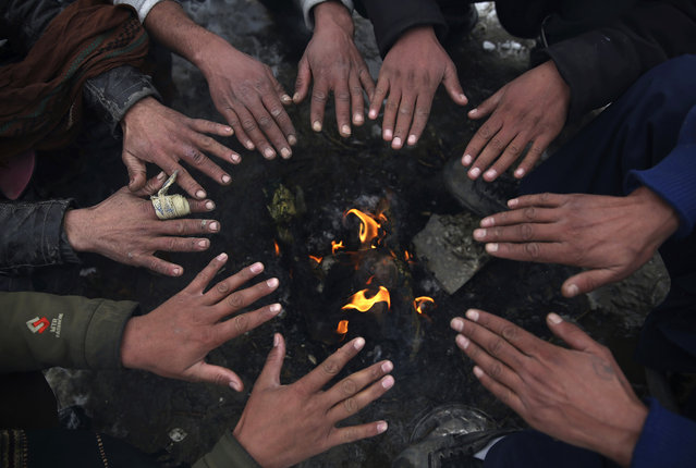 People sit around a fire to warm themselves after a heavy snowfall in Kabul, Afghanistan, Tuesday, January 14, 2020. Severe winter weather has struck parts of Afghanistan and Pakistan, with heavy snowfall, rains and flash floods that left dozens dead, officials said Monday as authorities struggled to clear and reopen highways and evacuate people to safer places. (Photo by Rahmat Gul/AP Photo)