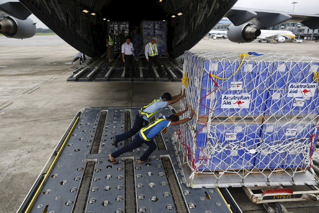 Workers unload aid from an Royal Australian Air Force (RAAF) transport plane carrying donated aid for Myanmar's flood victims at Yangon international airport in Yangon on August 10, 2015. (Photo by Soe Zeya Tun/Reuters)