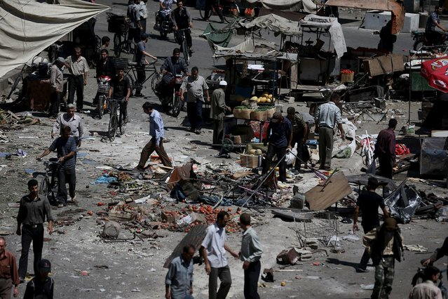People inspect the damage after what activists said were airstrikes by forces loyal to Syria's President Bashar al-Assad on a busy marketplace in the Douma neighborhood of Damascus, Syria August 12, 2015. (Photo by Bassam Khabieh/Reuters)