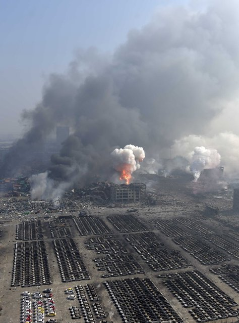 An aerial picture of smoke rising at the site of the explosions is seen at the Binhai new district, Tianjin, August 13, 2015. (Photo by Reuters/Xinhua)