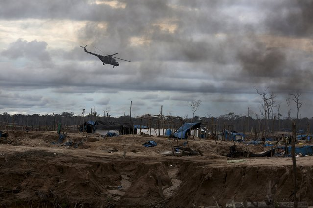 A helicopter patrols during a police operation to destroy illegal gold mining camps in La Pampa, in the southern Amazon region of Madre de Dios, Peru August 11, 2015. (Photo by Sebastian Castaneda/Reuters)