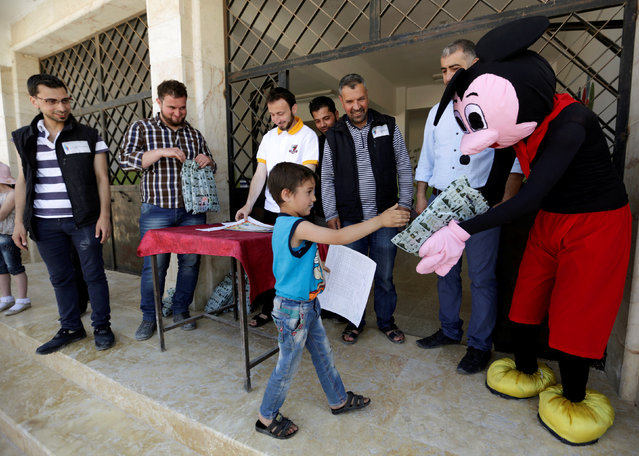 """A man dressed up as Mickey Mouse distributes certificates and gifts to students during a celebration marking the end of the school year, at """"Syria, The Hope"""" school on the outskirts of the rebel-controlled area of Maaret al-Numan town, in Idlib province, Syria June 1, 2016. The school is partially occupied and it teaches students until fourth grade. The building that is heavily damaged was used by government forces as a base before the rebel fighters took control of the area. (Photo by Khalil Ashawi/Reuters)"""