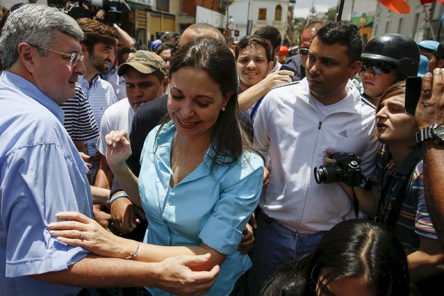 Venezuela's opposition leader Maria Corina Machado (C) greets supporters, after trying to register her candidacy for the upcoming parliamentary elections at an office of National Electoral Council (CNE), in Los Teques, Venezuela August 3, 2015. (Photo by Carlos Garcia Rawlins/Reuters)