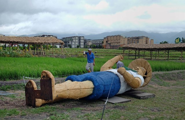 A worker walks past a 6.5-metre (21-foot) high scarecrow that has been secured to the ground before strong winds hit, at an organic farm in the town of Shanhsing in Ilan county as Typhoon Matmo approaches eastern Taiwan on July 22, 2014.  Typhoon Matmo churned towards Taiwan on July 22 picking up strength with thousands of tourists evacuated from outlying islands as weather forecasters warned of possible flash floods and landslides. (Photo by Sam Yeh/AFP Photo)