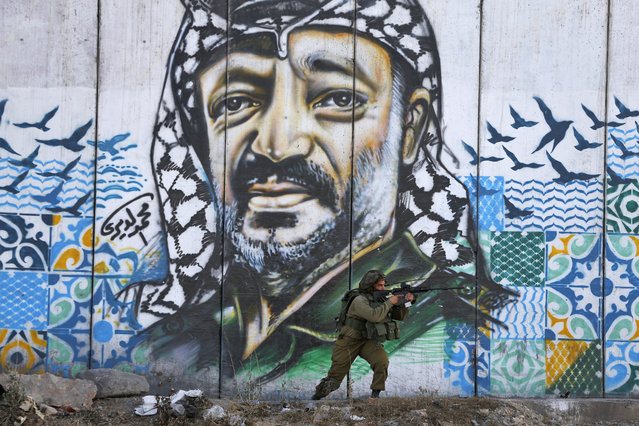 A member of the Israeli border guards looks through the scope of an assault rifle as he stands by a mural showing a graffiti image of late Palestinian leader Yasser Arafat, at the Qalandiya checkpoint near the West Bank city of Ramallah on July 19, 2017, during clashes after a protest by Palestinian youths against new Israeli security measures at the Al-Aqsa mosque compound, which include metal detectors and cameras, following an attack that killed two Israeli policemen. (Photo by Abbas Momani/AFP Photo)