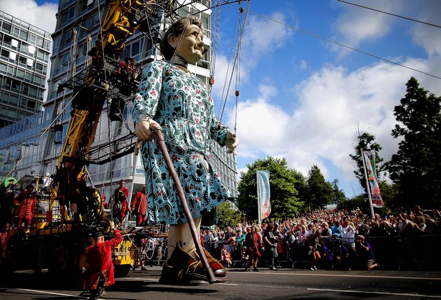"The Giant Grandmother walks through Liverpool as she takes part in Liverpool's World War I centenary commemorations, on Jule 27, 2014. The French street theatre company Royal de Luxe put on a show throughout the city from July 23-27. The giant puppet grandmother slept in St George's Hall for two days as part of ""Memories of August 1914"". As the giants tour the city the Little Girl Giant and her dog Xolo tell the story of the Liverpool Pals, the voluntary battalions from the city who served in WW1.  (Photo by Christopher Furlong/Getty Images)"