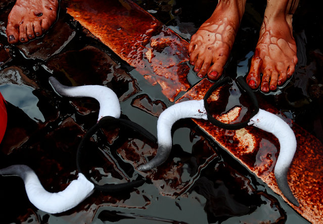 Fake blood runs down the bodies of animal rights protesters during a demonstration for the abolition of bull runs and bullfights a day before the start of the famous running of the bulls San Fermin festival in Pamplona, northern Spain, July 5, 2016. (Photo by Eloy Alonso/Reuters)