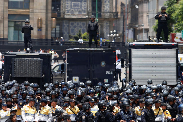 Riot police stand guard during a march from the National Coordination of Education Workers (CNTE) teachers' union against President Enrique Pena Nieto's education reform outside Bellas Artes museum in Mexico City, Mexico, July 6, 2016. (Photo by Edgard Garrido/Reuters)