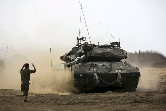 An Israeli soldier directs a tank during an exercise in the Israeli-occupied Golan Heights, near the ceasefire line between Israel and Syria, August 21, 2015. (Photo by Baz Ratner/Reuters)