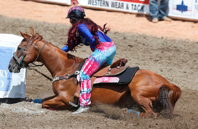 Fallon Taylor of Collinsville, Texas, slips and falls with her horse in the barrel racing event during the Calgary Stampede rodeo in Calgary, Alberta, Canada July 8, 2016. (Photo by Todd Korol/Reuters)