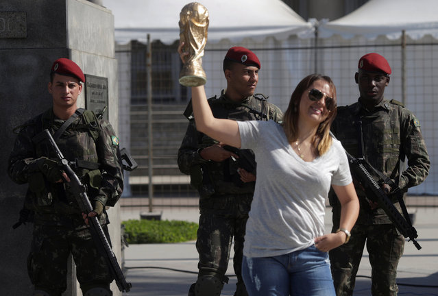 A woman poses with a replica of the soccer World Cup trophy as Brazilian Army soldiers attend a street patrolling exercise around the Maracana stadium ahead the 2016 Rio Olympics in Rio de Janeiro, Brazil, July 9, 2016. (Photo by Ricardo Moraes/Reuters)