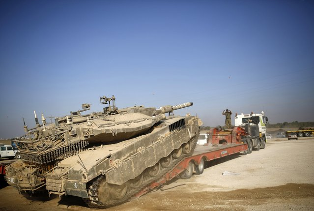 An Israeli soldier directs a tank onto a truck for transport near the border with Gaza August 6, 2014. A Gaza truce was holding on Wednesday as Egyptian mediators pursued talks with Israeli and Palestinian representatives on an enduring end to a war that has devastated the Hamas Islamist- dominated enclave. (Photo by Amir Cohen/Reuters)