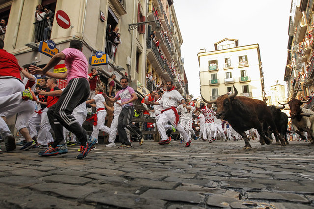 Revelers run in front of Jandilla's fighting bulls as they go on the way of the Estafeta corner during the fifth running of the bulls at the San Fermin Festival, in Pamplona, northern Spain, Monday, July 11, 2016. (Photo by Alvaro Barrientos/AP Photo)