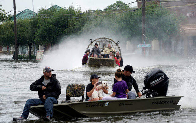 People are rescued from flood waters from Hurricane Harvey on an air boat in Dickinson, Texas on August 27, 2017. (Photo by Rick Wilking/Reuters)
