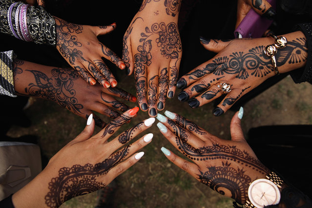 Girls show off their Henna tattoos during an Eid celebration  in Burgess Park on July 28, 2014 in London, England. The Muslim holiday Eid marks the end of 30 days of dawn-to-sunset fasting during the holy month of Ramadan. (Photo by Dan Kitwood/Getty Images)