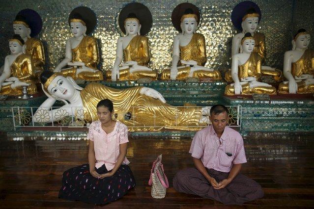 A woman and man meditate in Shwedagon pagoda in Yangon August 25, 2015. (Photo by Soe Zeya Tun/Reuters)