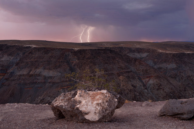 Lightning strikes near a ridge as a storm passes though Death Valley National Park in California just after sunset July 21, 2009. (Photo by Steve Marcus/Reuters)