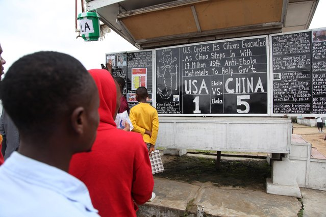 Liberians read the 'Daily Talk Chalk Board' headline story on the contributions between China and the USA to Liberia to combat the deadly Ebola virus in the country, Monrovia, Liberia, 19 August 2014. (Photo by Ahmed Jallanzo/EPA)