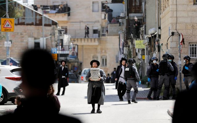 An ultra-Orthodox Jewish man carries trays of eggs as Israeli police patrol nearby to enforce government restrictions set in place to curb the spread of the coronavirus disease (COVID-19), in Mea Shearim neighborhood of Jerusalem on April 6, 2020. (Photo by Ronen Zvulun/Reuters)