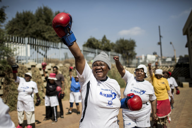 "The ""Boxing Gogos"" (Grannies) stretch as they take part in a session hosted by the ""A Team Gym"" in Cosmo City in Johannesburg on September 19, 2017. The grandmothers, many of whom are over 70 have been training with coach Claude Maphosa and claim that they no longer suffer from the ailments they had before, and are stronger than ever. The grannies travel from all over Cosmo City for the twice weekly sessions. Coach Maphosa is in the process of planning events in other areas for grannies who have been inspired by the story, to join in. (Photo by Gulshan Khan/AFP Photo)"