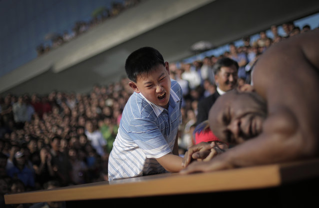 "A North Korean boy arm wrestles with former NFL player Bob ""The Beast"" Sapp Friday, August 29, 2014 in Pyongyang, North Korea. Former NFL player Sapp and a group of brawny pro wrestlers led by a Japanese politician took their oddball attempt at sports diplomacy to the streets of Pyongyang on Friday, staging a tug-war and arm wrestling competition with local children before a large and somewhat bewildered crowd of spectators. (Photo by Wong Maye-E/AP Photo)"