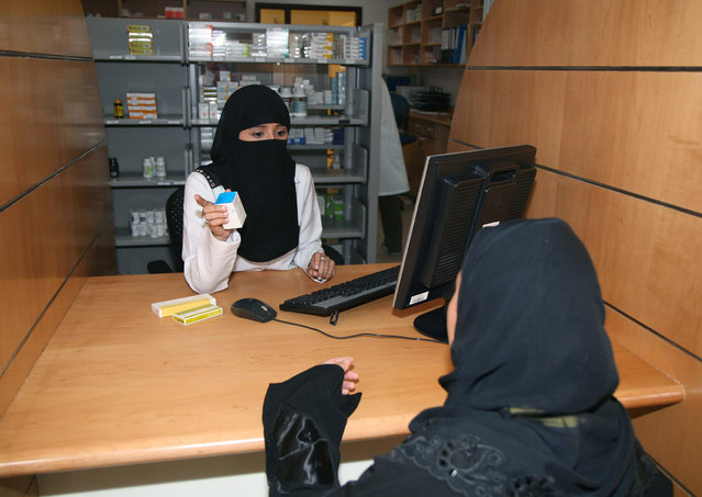 A female pharmacist (R) dispenses medicines at the International Medical Center in Jeddah, June 4, 2007. (Photo by Susan Baaghil/Reuters)