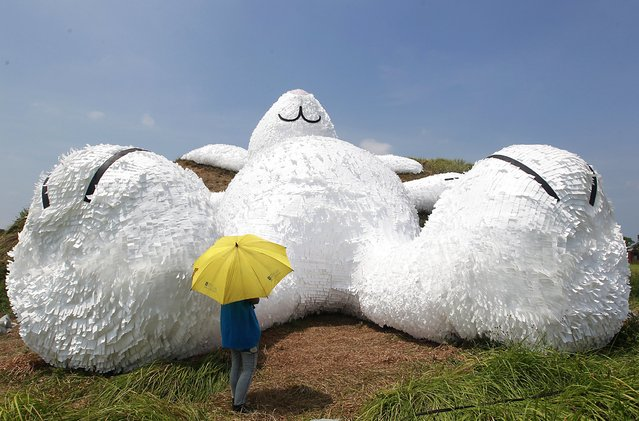 "A person stands in front of a 25.3-meter-long giant rabbit designed by Dutch artist Florentijn Hofman at an old aircraft hangar as part of the Taoyuan Land Art Festival in Taoyuan, northern Taiwan, September 3, 2014. The rabbit is named ""Moon rabbit"" for the coming Mid-Autumn Festival or the Moon Festival and will be displayed from September 4 to 14 at the Taoyuan military  base. (Photo by Pichi Chuang/Reuters)"