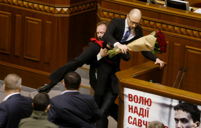 Rada deputy Oleg Barna removes Ukrainian Prime Minister Arseny Yatseniuk from the tribune, after presenting him a bouquet of roses, during the parliament session in Kiev, Ukraine, in this file picture taken December 11, 2015. (Photo by Valentyn Ogirenko/Reuters)