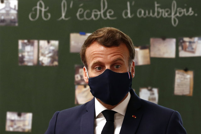 French President Emmanuel Macron, wearing a protective face mask, speaks with schoolchildren during a class at the Pierre Ronsard elementary school Tuesday, May 5 2020 in Poissy, outside Paris. Starting from May 11, all French businesses will be allowed to resume activity and schools will start gradually reopening. (Photo by Ian Langsdon/Pool via AP Photo)