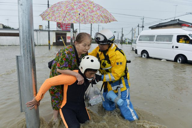 A woman is rescued by police officers at a residential area flooded by the Kinugawa river, caused by typhoon Etau in Joso, Ibaraki prefecture, Japan, in this photo taken by Kyodo September 10, 2015. Japan's weather agency extended its emergency warnings from the Tochigi Prefecture to Ibaraki, after severe rainfall caused floods and landslides on Thursday in eastern Japan, according to local media. (Photo by Reuters/Kyodo News)