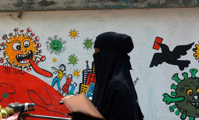A woman walks past a graffiti depicting the COVID-19 coronavirus during a government-imposed lockdown as a preventive measure against the COVID-19 coronavirus, in Narayanganj on May 18, 2020. (Photo by Munir Uz Zaman/AFP Photo)