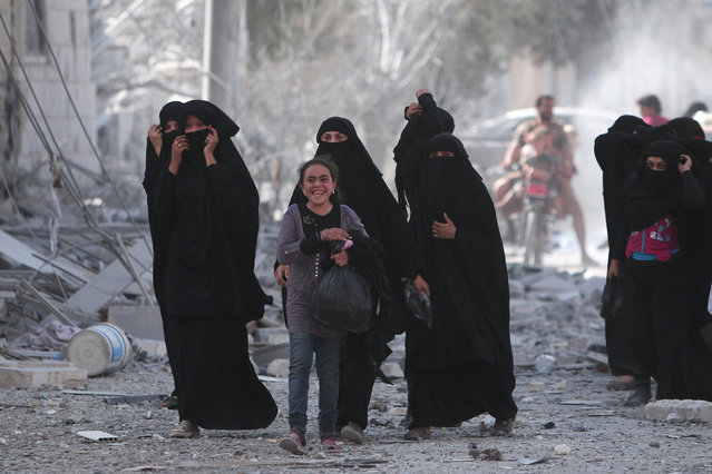 A girl smiles while walking along a rubble-strewn street with women after they were evacuated by the Syria Democratic Forces (SDF) fighters from an Islamic State-controlled neighbourhood of Manbij, in Aleppo Governorate, Syria, August 12, 2016. (Photo by Rodi Said/Reuters)