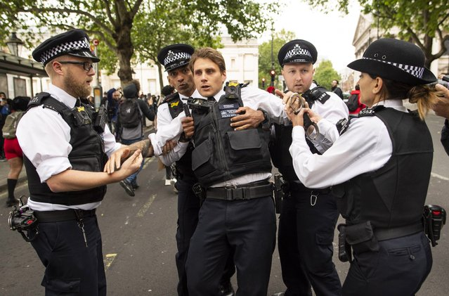 An injured police officer, who appeared to have been struck in the head by a thrown object, is assisted by his colleagues during a Black Lives Matter protest at Trafalgar Square on June 03, 2020 in London, England. The death of an African-American man, George Floyd, while in the custody of Minneapolis police has sparked protests across the United States, as well as demonstrations of solidarity in many countries around the world. (Photo by Justin Setterfield/Getty Images)
