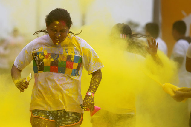 Participants are covered in colored powder as they compete in The Color Run in Lima, Peru, August 14, 2016. (Photo by Guadalupe Pardo/Reuters)