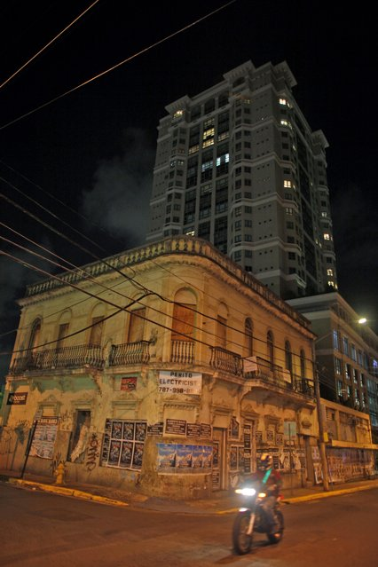 In this September 21, 2014 photo, an abandoned building sits in front of an upscale building in the Santurce neighborhood in San Juan, Puerto Rico. (Photo by Ricardo Arduengo/AP Photo)