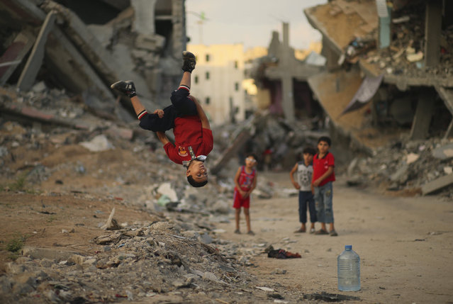 A Palestinian boy practices his Parkour skills near the ruins of houses, which witnesses said were destroyed during a seven-week Israeli offensive, in the Shejaia neighborhood east of Gaza City October 1, 2014. (Photo by Mohammed Salem/Reuters)